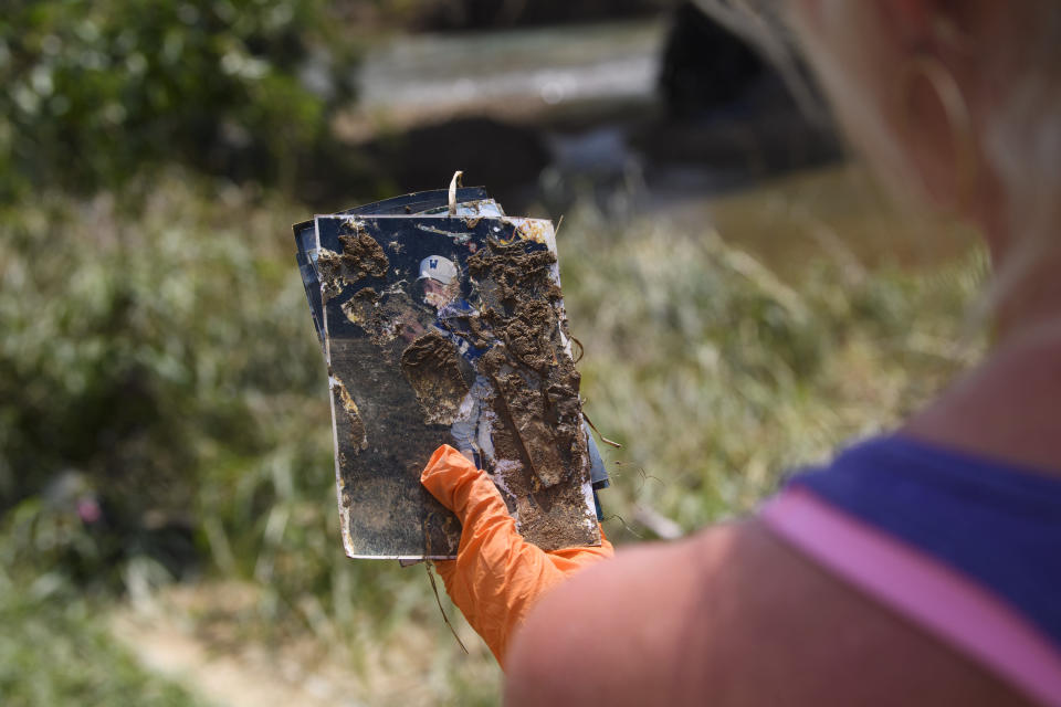 A woman holds a photo she found as she searches for personal items lost in recent flooding, Monday, Aug. 23, 2021, in Waverly, Tenn. Although she did not recognize the person in the photo she planned on posting it on social media to reconnect it with the owner. (AP Photo/John Amis)