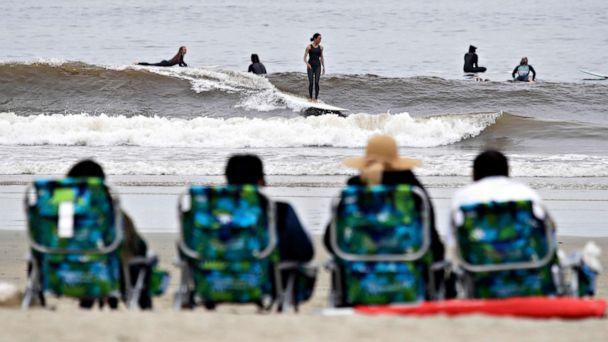 PHOTO:People sit on beach chairs and watch surfers, April 30, 2020, in Newport Beach, Calif. A memo sent to California police chiefs says Gov. Gavin Newsom will order all beaches and state parks closed starting May 1 to curb the spread of the coronavirus. (Marcio Jose Sanchez/AP)