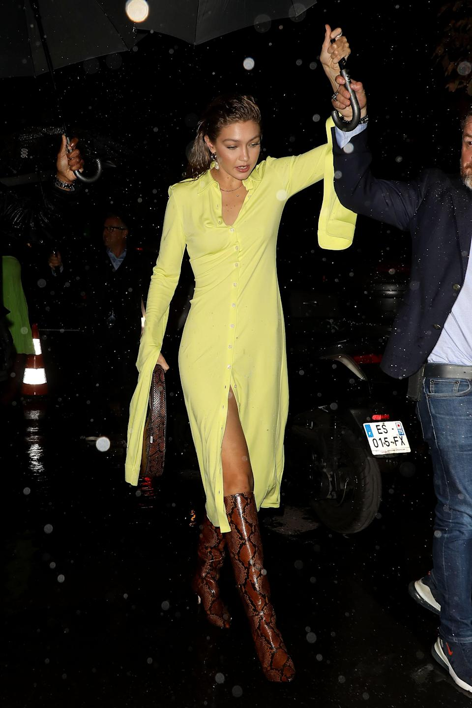 Attending the Fenty after party in Paris and little rain isn't going to keep Gigi from hitting the hottest party in Paris! Her love for exaggerated sleeves truly knows no bounds in this banana-yellow button-down midi dress. The unexpected pairing of a snakeskin handbag and matching boots kicks this look up from sweet to party-ready glam.