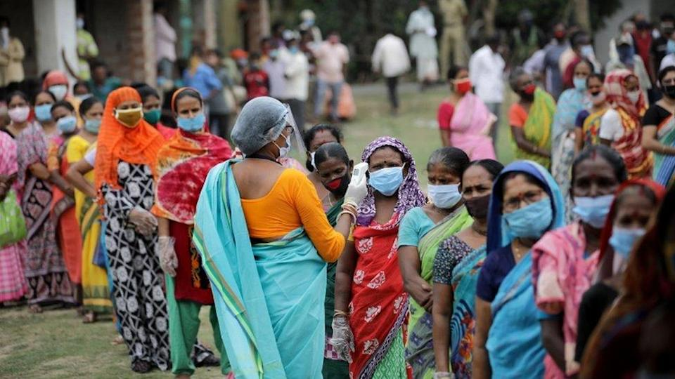 A health worker checks the temperature of women queuing outside a polling station during the sixth phase of the 2021 West Bengal Legislative Assembly election at Kampa village.