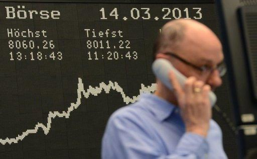 A trader speaks on the phone in frotn of a board displaying Germany's share index DAX on March 14, 2013