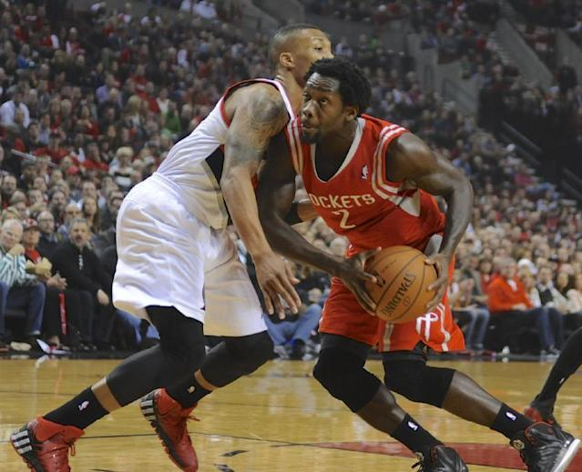 Houston Rockets' Patrick Beverley (2) looks to shoot against Portland Trail Blazers' Damian Lillard (0) during the first half of game four of an NBA basketball first-round playoff series game in Portland, Ore., Sunday March 30, 2014. (AP Photo/Greg Wahl-Stephens)
