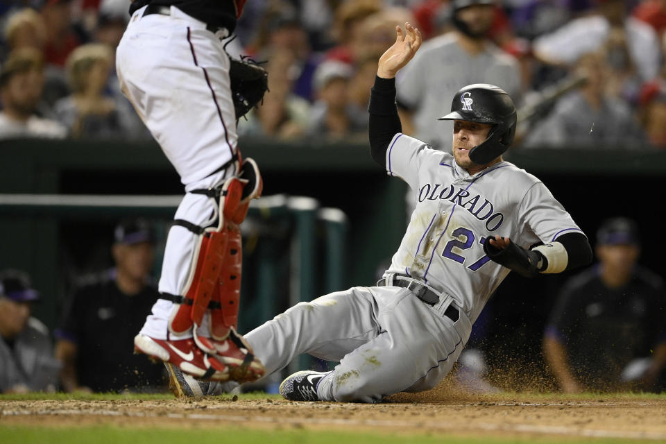 Colorado Rockies' Trevor Story (27) slides home to score on a single by Ryan McMahon during the sixth inning of a baseball game against the Washington Nationals, Friday, Sept. 17, 2021, in Washington. (AP Photo/Nick Wass)