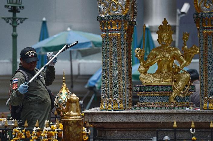 An EOD policeman inspects the cordoned-off site of a bomb blast at the popular Erawan shrine in Bangkok on August 18, 2015 (AFP Photo/Christophe Archambault)