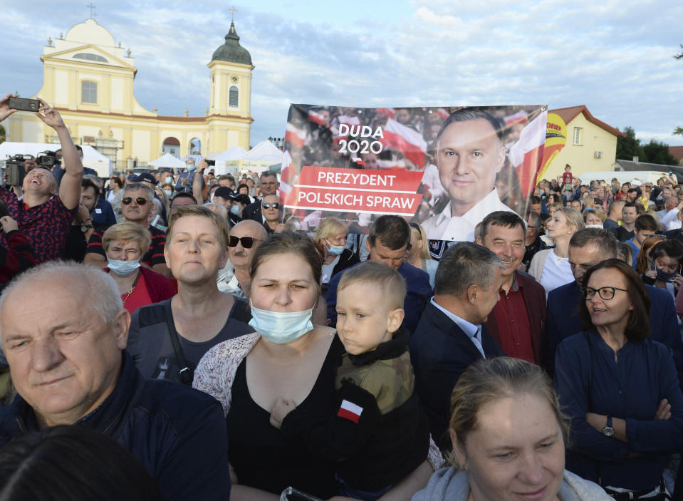 Supporters of Polish President Andrzej Duda hold up banners at a presidential election campaign rally in Tykocin, Poland, Tuesday, July 7, 2020. Two bitter rivals are heading into a razor's-edge presidential runoff election Sunday in Poland that is seen as an important test of populism in Europe after a campaign that exacerbated a conservative-liberal divide in the country. (AP Photo/Czarek Sokolowski)