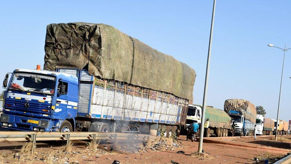 Trucks loaded with goods wait to cross the border in Cinkasse, the northern Togo commercial border post with Burkina Faso, on February 16, 2020