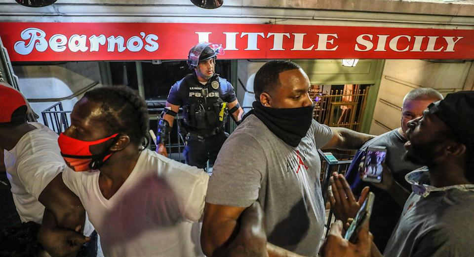 """Five men, including Christopher Gales, Darren Lee Jr, Ricky McClellan and Julian """"New Heightz"""" De La Cruz linked arms to keep a crowd of protesters away from LMPD officer Galen Hinshaw on the first night of protests in Louisville on May 28, 2020."""