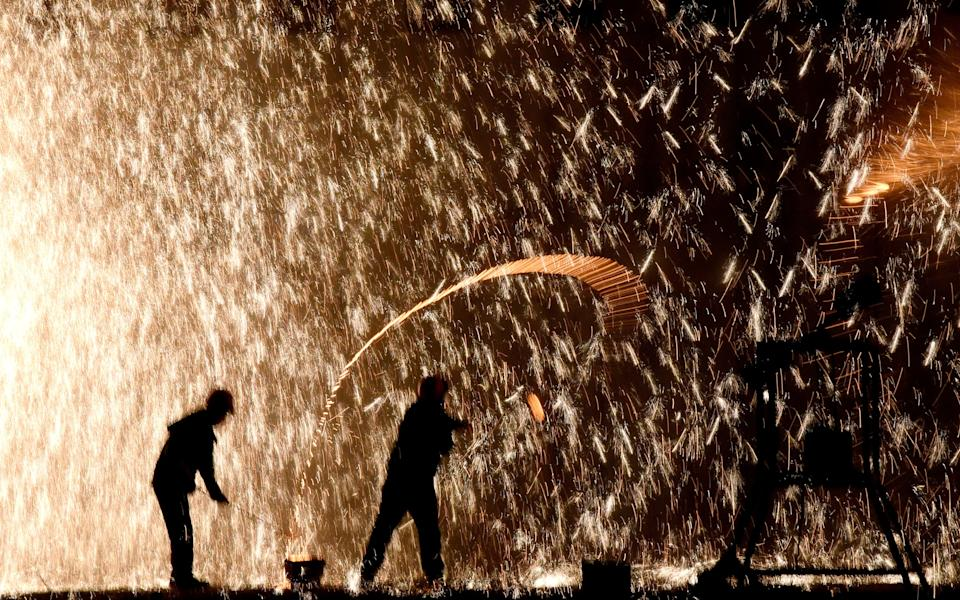 """HANDAN, CHINA - JANUARY 19, 2020 - Craftsman in """"fighting iron flower"""", Handan City, Hebei Province, China, on the evening of January 19, 2020. """"Beating iron flower"""" is a scene of """"iron flower fire rain"""" in the air after turning pig iron into molten iron with a small iron smelting furnace, and then beating the molten iron with sawdust on the sky with a board. - PHOTOGRAPH BY Costfoto / Barcroft Media (Photo credit should read Costfoto / Barcroft Media via Getty Images)"""