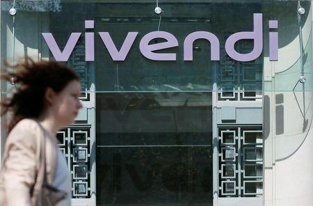 A woman walks walk past the main entrance of the entertainment-to-telecoms conglomerate Vivendi's headquarters in Paris