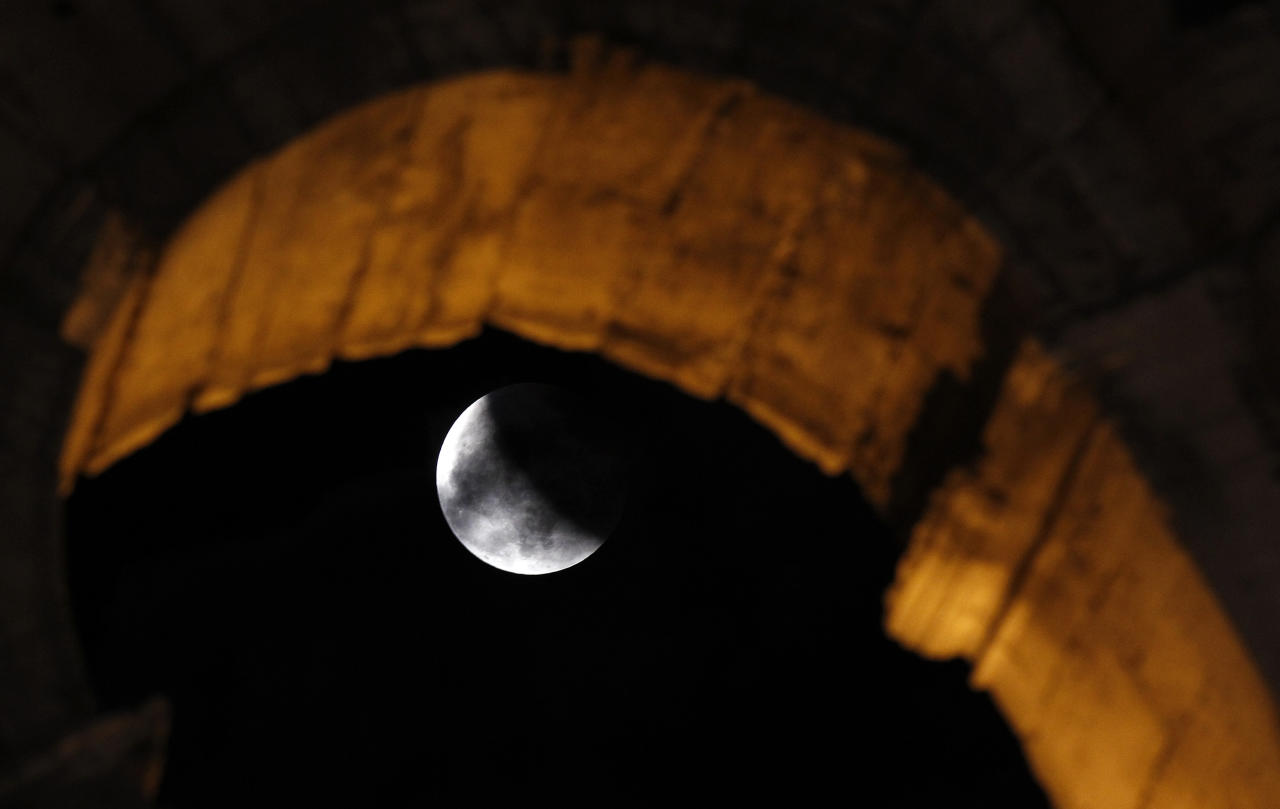 A shadow falls on the moon during a lunar eclipse, at the ancient Colosseum in Rome June 15, 2011.  REUTERS/Alessandro Bianchi