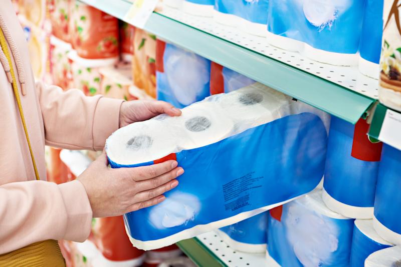 Toilet paper in the hands of the buyer in the store