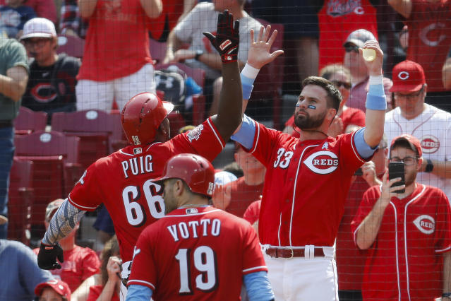 Cincinnati Reds' Yasiel Puig (66) celebrates with Jesse Winker (33) after hitting a two-run home run off Texas Rangers relief pitcher Peter Fairbanks in the fourth inning of a baseball game, Sunday, June 16, 2019, in Cincinnati. (AP Photo/John Minchillo)