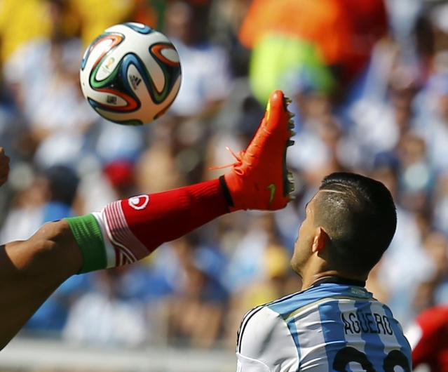 Iran's Mehrdad Pouladi (L) fights for the ball with Argentina's Sergio Aguero during their 2014 World Cup Group F soccer match at the Mineirao stadium in Belo Horizonte June 21, 2014. REUTERS/Kai Pfaffenbach (BRAZIL - Tags: SOCCER SPORT WORLD CUP TPX IMAGES OF THE DAY) TOPCUP