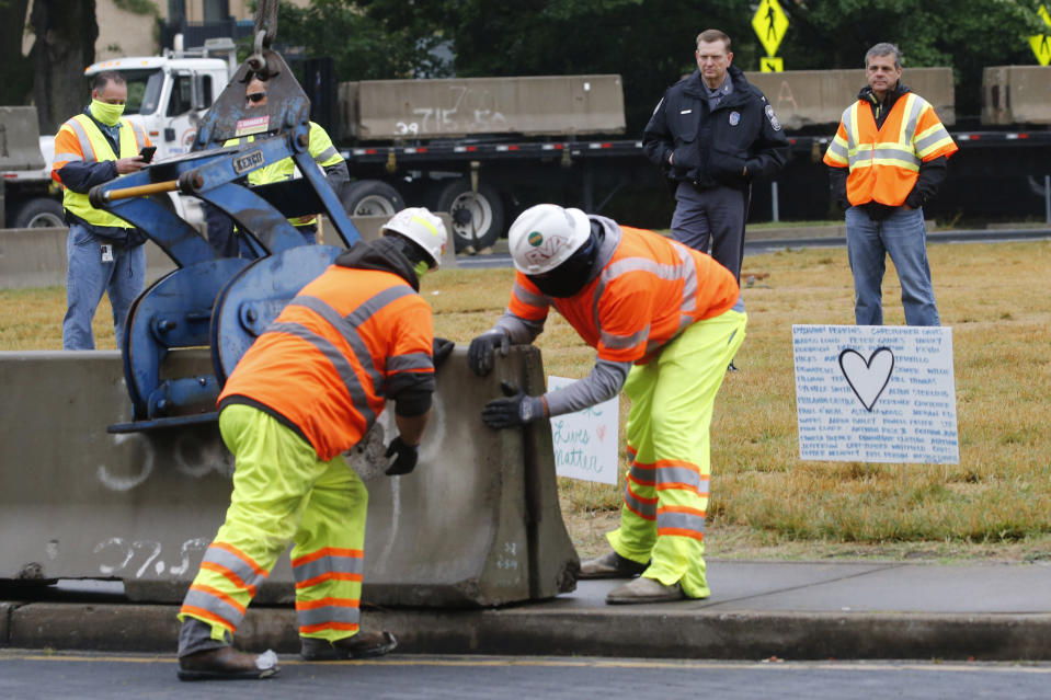 Capitol Police Superintendent Col. Steve Pike, top second from right, and director of The Virginia Department of General Services, Joe Damico, top right, watch as workers install concrete barriers around the statue of Confederate General Robert E. Lee on Monument Avenue Wednesday, June 17, 2020, in Richmond, Va. The barriers are intended to protect the safety of demonstrators as well as the structure itself. (AP Photo/Steve Helber)