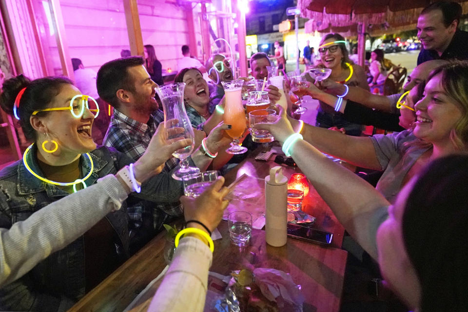 """Emily Baumgartner, left, and Luke Finley, second from left, join friends from their church group in a birthday toast to one of the members, upper right, during their weekly """"Monday Night Hang"""" gathering at the Tiki Bar on Manhattan's Upper West Side Monday, May 17, 2021, in New York. """"Most of us live alone. and we need community. During the pandemic, we started hanging out in the park (Central Park) once a week. Once bars and restaurants reopened, we started coming back to Tiki Bar afterward. Under the latest regulations, vaccinated New Yorkers can shed their masks in most situations Wednesday. (AP Photo/Kathy Willens)"""
