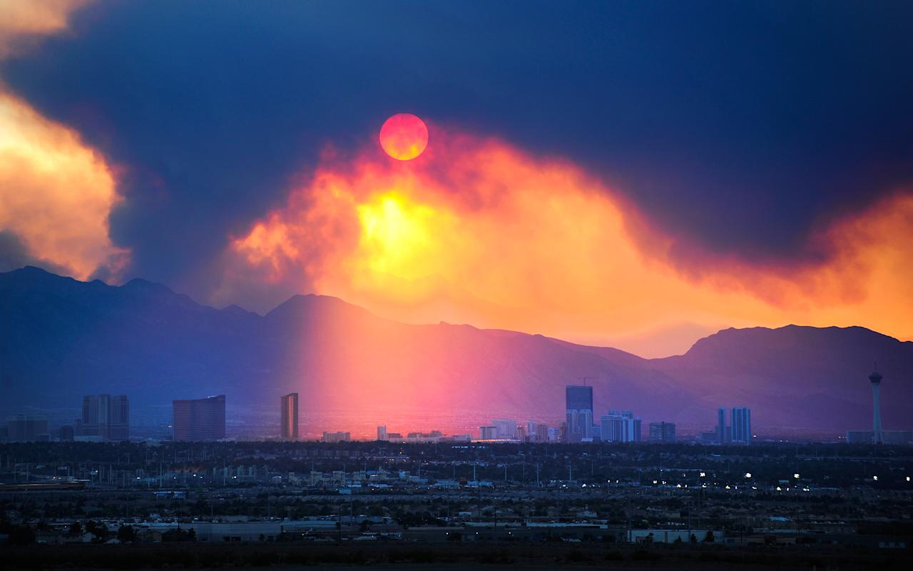 The sun shines over the Las Vegas Strip skyline as smoke continues to billow from the Carpenter 1 fire on Mount Charleston on Monday, July 8, 2013 in Las Vegas. Homes were threatened, but more than 750 firefighters, including 18 elite Hotshot crews, were battling the Carpenter 1 Fire some 25 miles northwest of Las Vegas, said Jay Nichols, a U.S. Forest Service spokesman in the Spring Mountains National Recreation Area. (AP Photo/Las Vegas Review-Journal, David Becker)