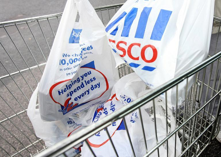 A shopper loads shopping plastic bags into a trolley at a Tesco store in Liverpool on October 3, 2006 (AFP Photo/Paul Ellis)