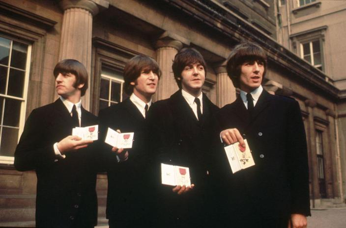 """<p>Even though this wasn't The Beatles' first time meeting the Queen (they performed for her in 1963 and John Lennon famously told her to """"<a href=""""https://www.youtube.com/watch?v=rvBCmY7wAAU"""" rel=""""nofollow noopener"""" target=""""_blank"""" data-ylk=""""slk:just rattle your jewelry"""" class=""""link rapid-noclick-resp"""">just rattle your jewelry</a>"""" while they played """"Twist and Shout,"""" lol), this was the most honorable occasion. The Queen awarded them The Most Excellent Order of the British Empire (OBE) in 1965 and they sported classic black suits for the event, naturally.</p>"""
