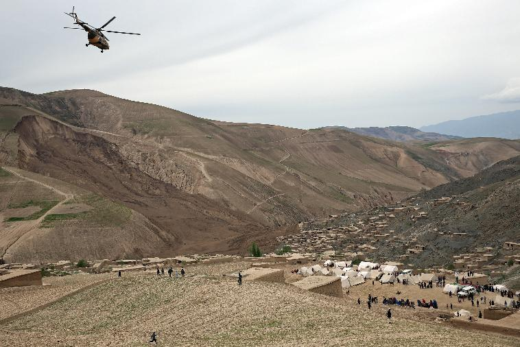 In this Sunday, May 4, 2014 photo, Survivors walk near the site of Friday's landslide that buried Abi-Barik village in Badakhshan province, northeastern Afghanistan. The landslide was likely triggered by heavy rains that have fallen across northern Afghanistan in recent weeks. It broke off such a massive chunk of earth, burying hundreds of homes, that officials have said it will be impossible to bring up all the bodies. Still, many villagers have continued digging on their own. (AP Photo/Massoud Hossaini)