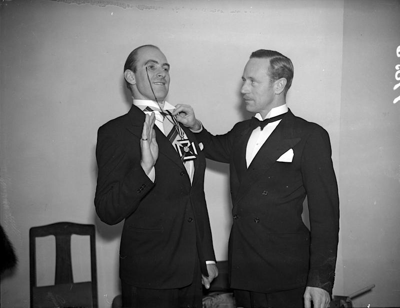 October 1939: Film star Leslie Howard (1890 - 1943) presenting the Iron Cross to a 'Lord Haw Haw' impersonator. (Photo by Stroud/London Express/Getty Images)