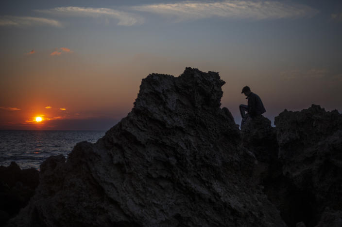 A boy sits on a rock as the sun sets over the Mediterranean Sea, in Gador nature reserve near Hadera, Israel, Sunday, Feb. 21, 2021. Israel has closed its Mediterranean beaches following an offshore oil spill that has devastated the country's coastline in what officials are calling one of the country's worst ecological disasters. The Environmental Protection, Health and Interior Ministries issued a joint statement Sunday warning the public not to visit beaches. (AP Photo/Ariel Schalit)