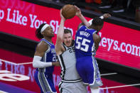 San Antonio Spurs center Jakob Poeltl (25) is fouled by Sacramento Kings guard Delon Wright (55) while Kings center Richaun Holmes (22) defends during the first quarter of an NBA basketball game in Sacramento, Calif., Friday, May 7, 2021. (AP Photo/Hector Amezcua)