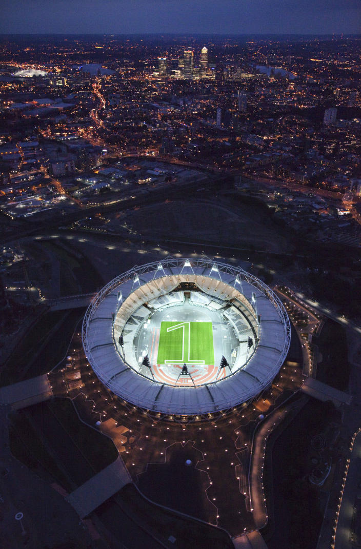 """In this image made available July 25, 2011 by the London Organising Committee of the Olympic and Paralympic Games (LOCOG), an aerial photo of the London 2012 Olympic Stadium to mark """"1 year to go to the Olympic Games"""" is seen in London. The number one mown into the grass in the Olympic Stadium indicates the start the celebrations for the """"1 year to go"""" milestone. (AP Photo/LOCOG, Anthony Charlton)"""