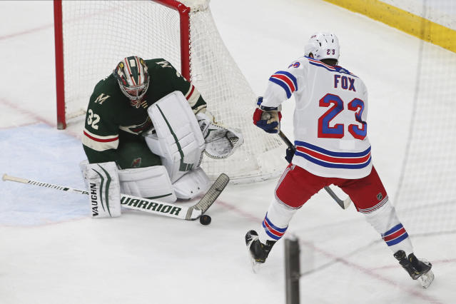 Minnesota Wild's Alex Stalock, left, stops a shot by New York Rangers' Adam Fox during the first period of an NHL hockey game Thursday, Feb. 13, 2020, in St. Paul, Minn. (AP Photo/Jim Mone)