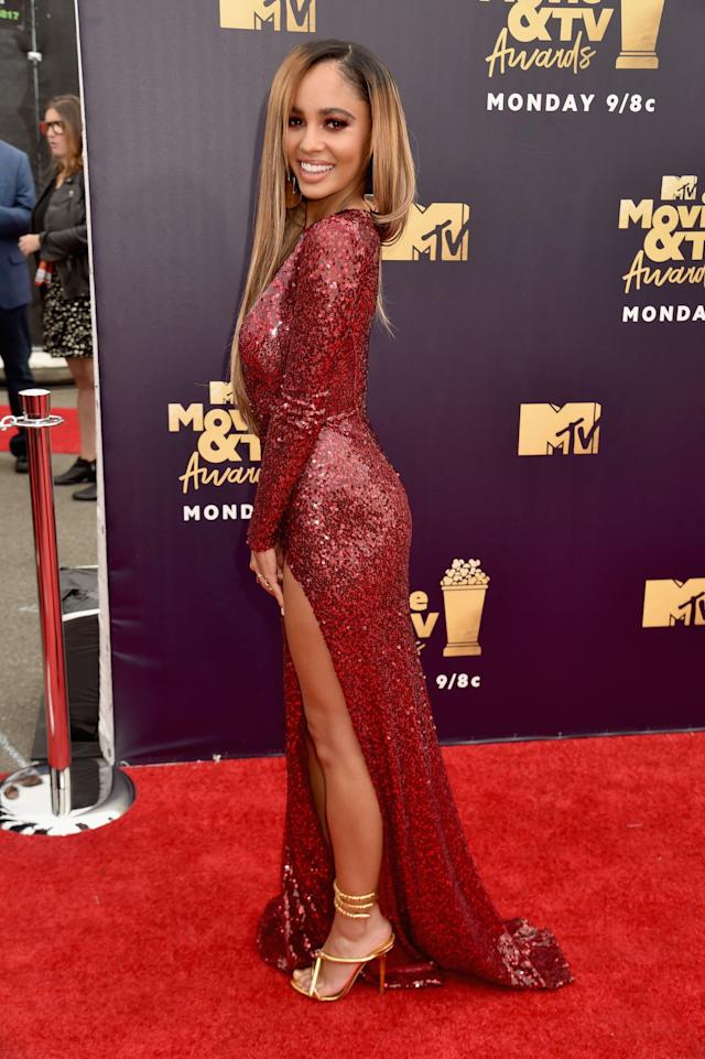 <p>Wearing a sparkly red gown.</p>