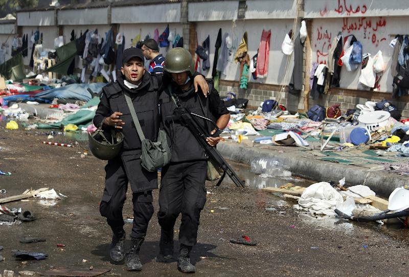 A bleeding Egyptian riot policeman is helped by a comrade during clashes as security forces moved in to disperse supporters of  ousted president Mohamed Morsi in a huge camp near Rabaa al-Adawiya mosque in eastern Cairo on August 14, 2013