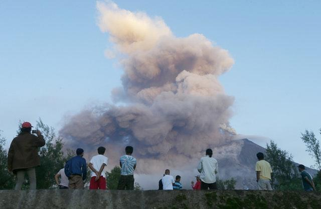 Residents watch as the Mayon volcano erupts anew as seen from Legazpi city, Albay province, around 200 miles south east of Manila, Philippines, in 2018