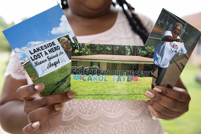 Shenika Jackson holds photos memorializing her late mother, Carol Faye Doby, who died from complications of COVID-19 earlier this year, in Bolton, Miss.