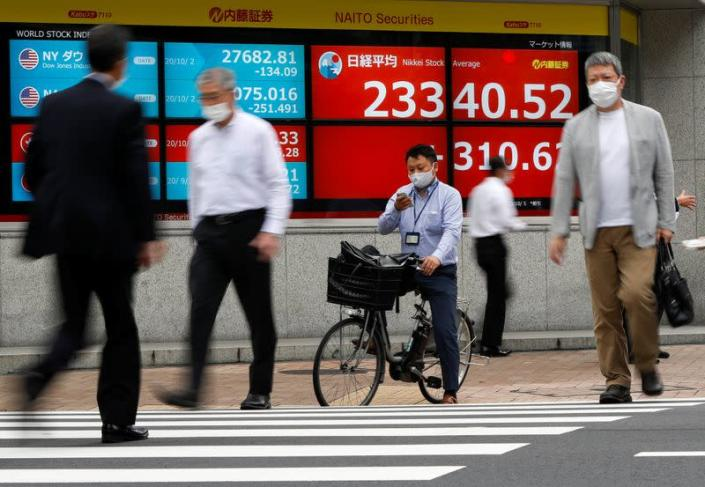 Passersby wearing protective face masks walk past a screen displaying Nikkei share average and world stock indexes, amid the coronavirus disease (COVID-19) outbreak, in Tokyo