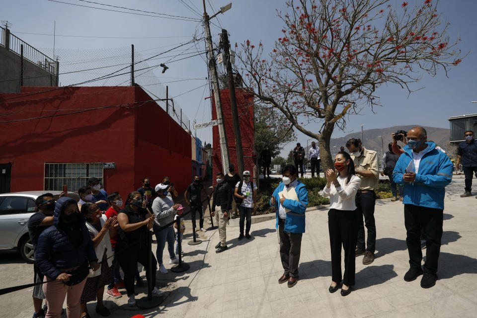 Mexico City Mayor Claudia Sheinbaum greets neighborhood residents who gathered to watch from a distance during the inauguration of a new aerial public transit system dubbed the Cablebus, at the Campos Revolucion station in the Cuautepec neighborhood of northern Mexico City, Thursday, March 4, 2021. For the residents of Cuautepec, this new system, the first of four planned lines, will turn a commute to the nearest subway station, that can last up to two hours, into a 30-minute ride. (AP Photo/Rebecca Blackwell)