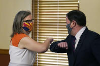 Arizona Secretary of State Katie Hobbs, left, and Arizona Gov. Doug Ducey bump elbows as they meet to certify the election results for federal, statewide, and legislative offices and statewide ballot measures at the official canvass at the Arizona Capitol Monday, Nov. 30, 2020, in Phoenix. (AP Photo/Ross D. Franklin, Pool)