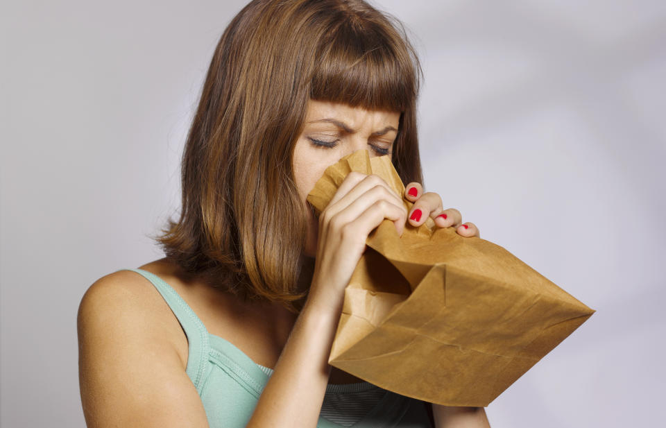 woman having a panic attack using paper bag to calm herself