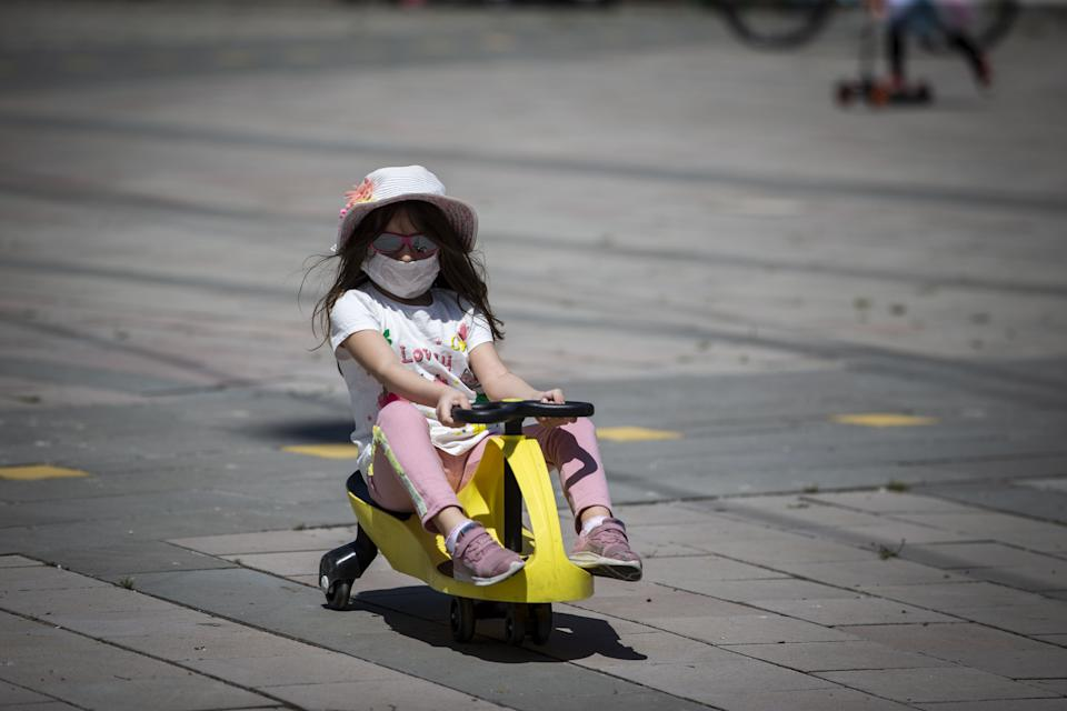 ANKARA, TURKEY - MAY 13: Kids enjoy outdoor time at Tunali Hilmi Street after children under 14 years across Turkey allowed to leave their homes, remaining within walking distance and wearing masks, on May 13 between 11 a.m. and 3 p.m. local time, in Ankara, Turkey on May 13, 2020. Turkey on Wednesday eased coronavirus (Covid-19) restrictions for young people under 14 years old. (Photo by Binnur Ege Gurun Kocak/Anadolu Agency via Getty Images)