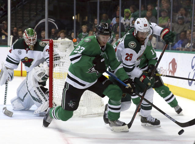 Dallas Stars defenseman Esa Lindell (23) and Minnesota Wild defenseman Greg Pateryn (29) battle for the puck in the first period of an NHL hockey game Saturday, April 6, 2019, in Dallas. (AP Photo/Richard W. Rodriguez)