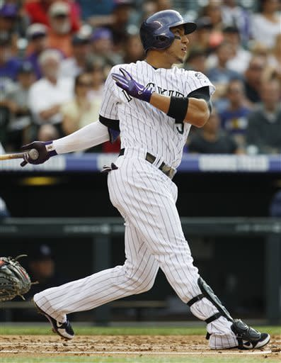 Colorado Rockies' Carlos Gonzalez follows the flight of his long fly-out against the San Diego Padres in the first inning of a baseball game in Denver, Saturday, June 8, 2013. (AP Photo/David Zalubowski)