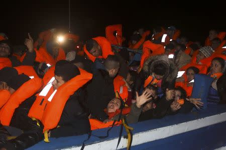 Migrants onboard a drifting overcrowded wooden boat react during a rescue operation by the Spanish NGO Proactiva Open Arms, north of the Libyan city of Sabratha in central Mediterranean Sea, March 29, 2017.  REUTERS/Yannis Behrakis