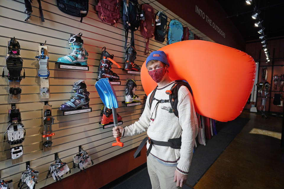 Cameron French, from White Pine Touring, wears an Ascent 40 AVABAG avalanche backpack on Dec. 18, 2020, in Park City, Utah. With another ski season getting underway, avalanche forecasters and search-and-rescue groups are concerned that large numbers of skiers and snowboarders will again turn to the backcountry to avoid crowds and reservation systems at resorts. The increased interest in the backcountry has been a lifeline for the outdoor retail industry amid the pandemic, but it has also renewed a push among gear manufacturers and stores to sell responsibly. (AP Photo/Rick Bowmer)