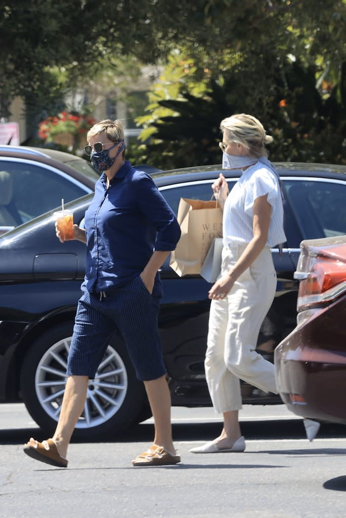 """EXCLUSIVE: Ellen DeGeneres and Portia DeRossi who have been staying inside their fancy home in Santa Barbara, take a break from being cooped up what Ellen described as, her """"prison"""" and head out in their convertible Porsche. The 62 year-old comedian and her 47 year-old wife are spotted enjoying a bit of a wander around Santa Barbara on Memorial Day while wearing masks to guard against possible spreading coronavirus. Seen here heading back to their car, Portia is carrying a bag from Wendy Foster where she seemed like one particular dress. She'd modeled it for Ellen, who pulled her mask down to drink her iced-tea while watching. 23 May 2020 Pictured: Ellen Degeneres, Portia DeRossi. Photo credit: Rachpoot/P&P/MEGA TheMegaAgency.com +1 888 505 6342 (Mega Agency TagID: MEGA670855_001.jpg) [Photo via Mega Agency]"""