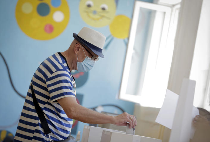 A woman casts her her vote at a polling station in Sofia, Sunday, July 11, 2021. Bulgarians are voting in a snap poll on Sunday after a previous election in April produced a fragmented parliament that failed to form a viable coalition government. (AP Photo/Valentina Petrova)