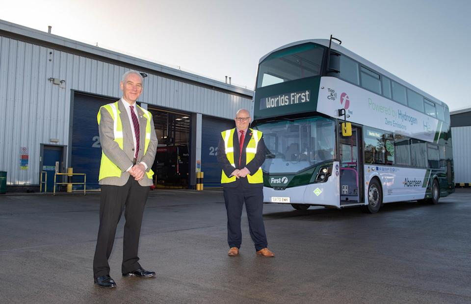 Operations Director for First Aberdeen, David Phillips (R) and Councillor Philip Bell pose alongside a world first hydrogen powered, zero emission double-decker bus in Ellon in Aberdeenshire