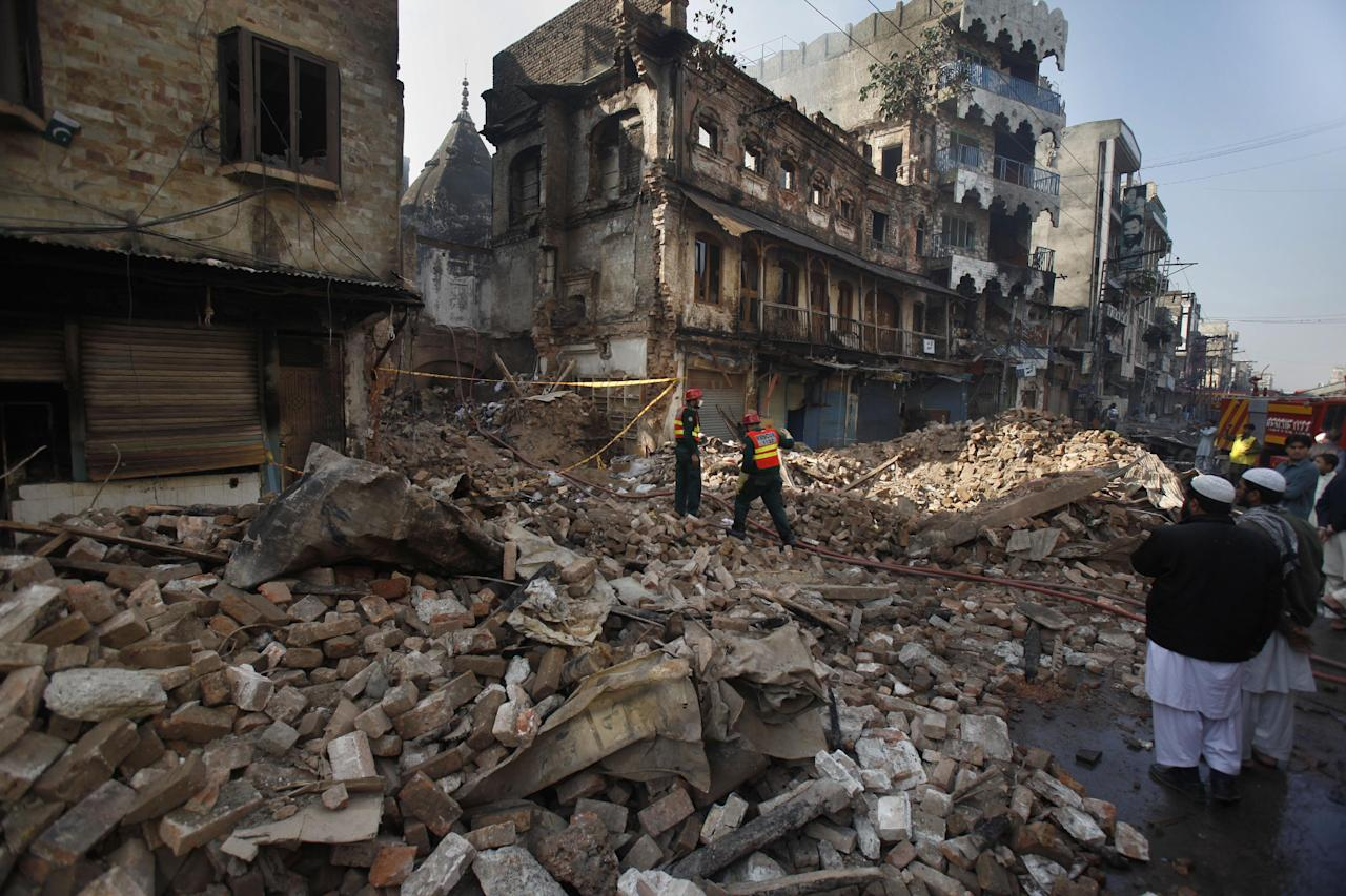 Pakistani rescue workers walk through the rubble while people look a burnt building, which was torched in the Friday's sectarian clashes, in Rawalpindi, Pakistan, Monday, Nov. 18, 2013. Pakistani police say the government has lifted a curfew in the garrison city of Rawalpindi that was imposed after eight Sunni Muslims were killed in a sectarian clash with Shiites marching in a religious procession. (AP Photo/Anjum Naveed)
