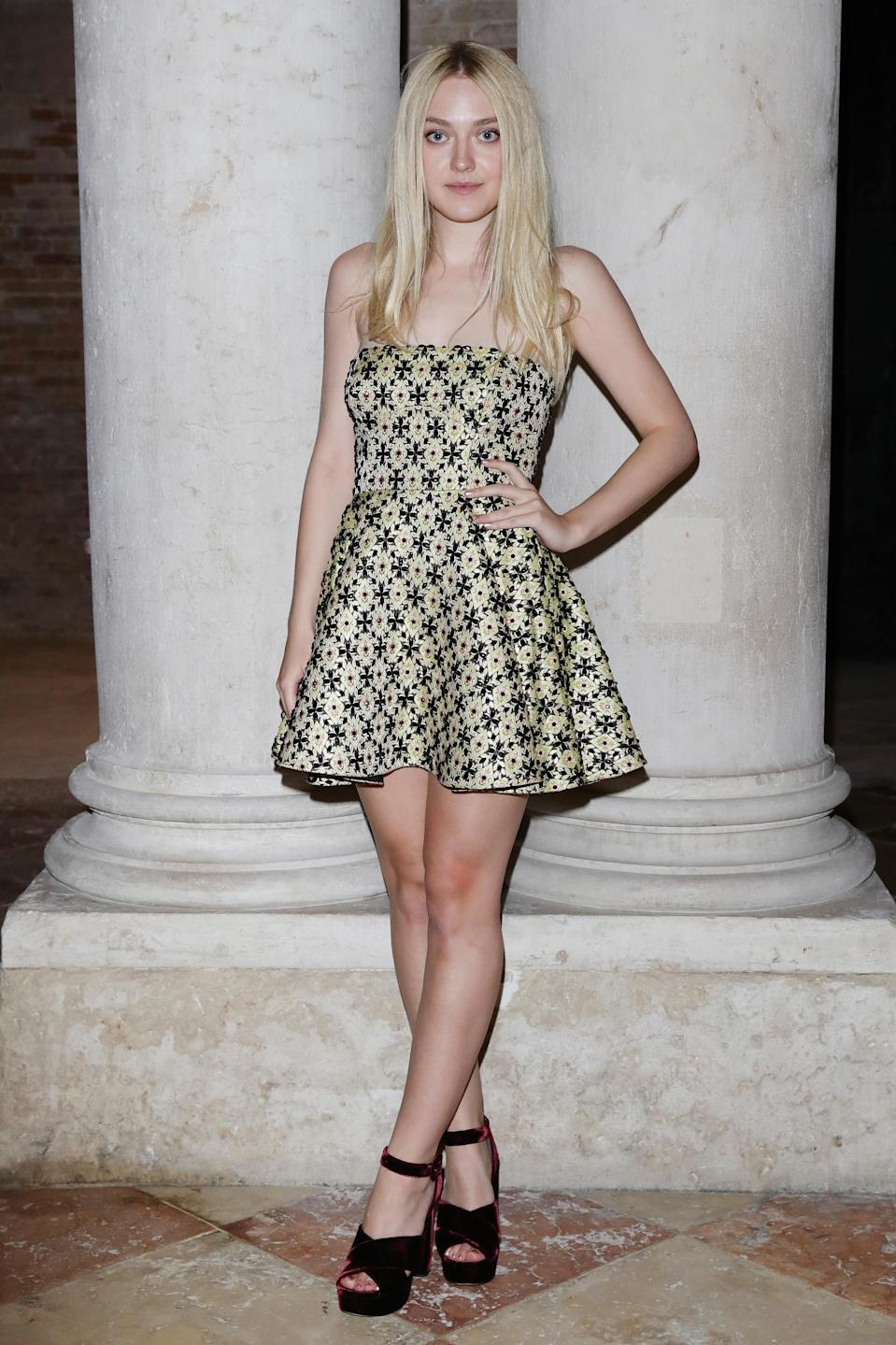 <p>Dakota Fanning rarely puts a sartorial step wrong and we're seriously into her latest look at Venice Film Festival. For the Miu Miu dinner, she teamed a cold-shoulder mini dress with velvet platforms by the label. <em>[Photo: Getty]</em> </p>