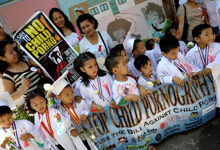 Filipino children walk together with their parents during an anti-child pornography protest march in Manila, on March 10, 2009