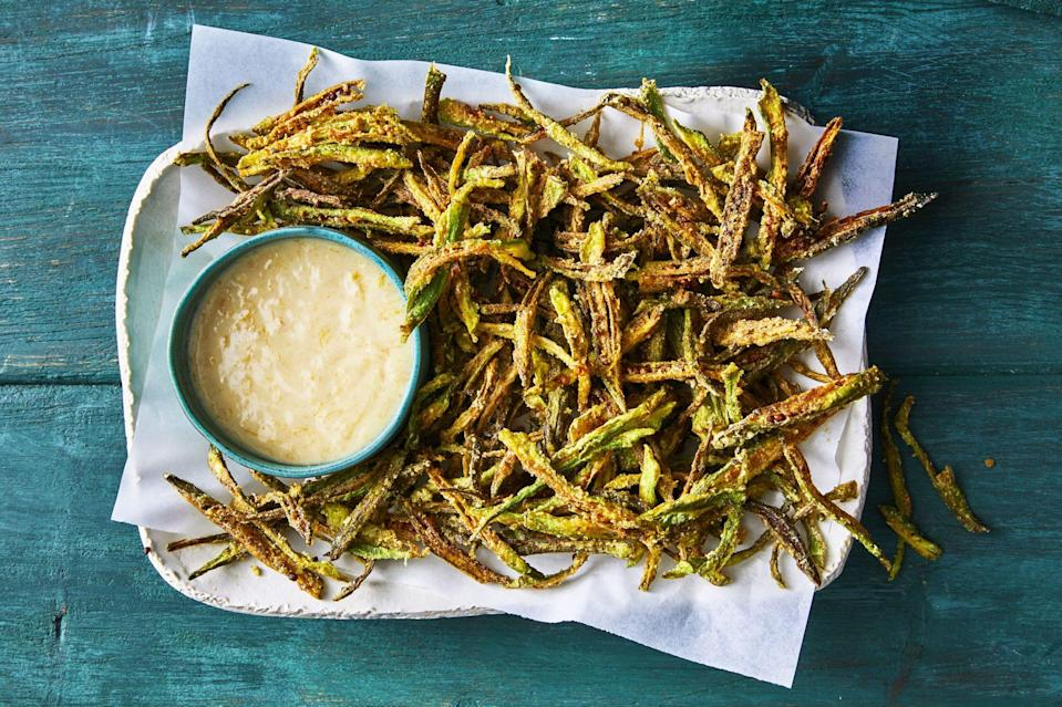 """<p><strong>Recipe:</strong> <a href=""""https://www.southernliving.com/recipes/curried-okra-shoestring-fries"""" rel=""""nofollow noopener"""" target=""""_blank"""" data-ylk=""""slk:Curried Okra Shoestring Fries"""" class=""""link rapid-noclick-resp"""">Curried Okra Shoestring Fries</a></p> <p>A mixture of curry powder, salt, and cornstarch make these Curried Okra Shoestring Fries irresistible. Prepare them for your next cookout as the ultimate crunchy side dish.</p>"""