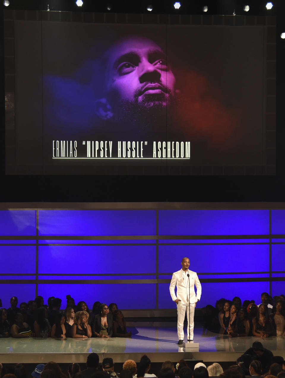 """FILE - This June 23, 2019 file photo shows Tip """"T.I."""" Harris presents the humanitarian award to late rapper Nipsey Hussle at the BET Awards in Los Angeles. Hussle, 33, was shot and killed outside his Los Angeles clothing store on March 31, 2019. A year after Hussle's death, his popularity and influence are as strong as ever. He won two posthumous Grammys in January, he remains a favorite of his hip-hop peers and his death has reshaped his hometown of Los Angeles in some unexpected ways. (Photo by Chris Pizzello/Invision/AP, File)"""