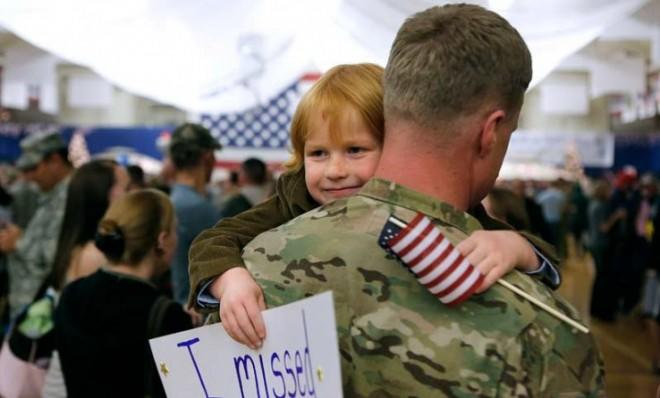 A child hugs his father, who returned from Afghanistan on Nov. 4, 2012, after a nine-month deployment.